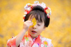 七五三参りの後でイチョウの落ち葉でおどけて遊ぶ女の子
