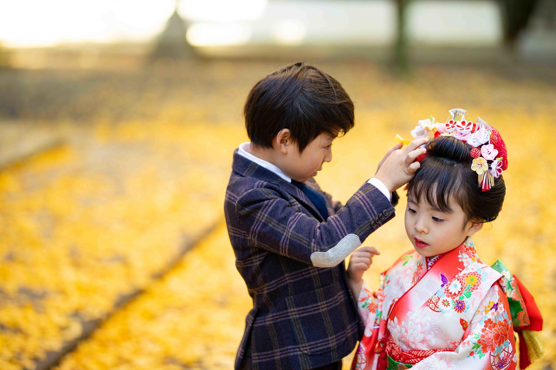 落ち葉を妹の頭に飾ってあげる兄
