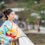 嵐山の渡月橋を振り返らずに渡る、着物を着た少女の写真